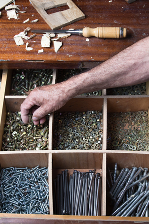 compartments: Desk drawer of a cabinetmaker working with several compartments with nuts, screws, nails, bolts  the drawer screws Stock Photo