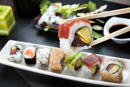 箸を使って寿司ロールを食べるテーブル レストランで巻き寿司の部分を取って箸のクローズ アップ