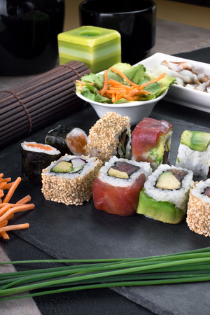 closeup vertical of platter with sushi menu assorted on the table restaurant  detail sushi rolls prepared on plate