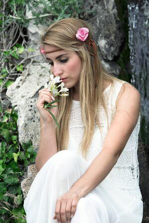 femme romantique: belle et sensuelle femme avec de longs cheveux blonds l'odeur des fleurs du jardin portrait mélancolique de femme fleurs sentant jolie blonde