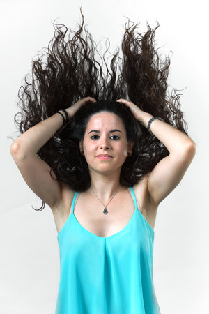 uncombed: girl blowing her long black hair in whit background  woman brunette moving her amazing long hair