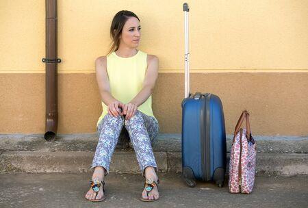 valise voyage: belle jeune fille assise dans la rue avec leurs valises en attente pour voyager Jolie femme avec une valise de voyage en attente dans la rue