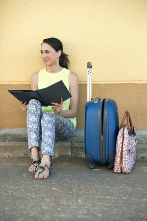 displacement map: attractive woman traveling with bags, reading a travel guide sitting on the sidewalk while waiting  young woman tourist sitting with luggage and a travel brochure in hand