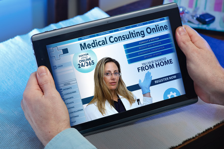 healthcare professional: man searching web internet for recruitment health insurance on internet with tablet in you home  hands of a man at a website of online health service in the tablet