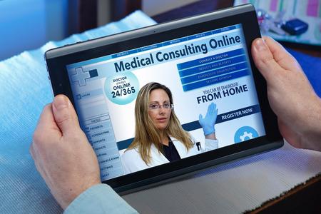 uomo alla ricerca internet web per l'assicurazione sanitaria di reclutamento su internet con tavoletta in voi a casa mani di un uomo in un sito di servizio sanitario in linea nel tablet