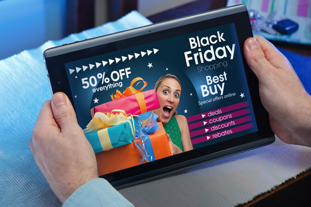 black: man searching website internet store to purchase gifts online in Black Friday with your tablet in you home  hands of a man at a website with an announcement concept for black friday deals