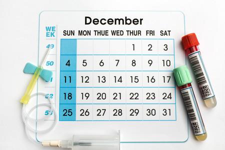 12 2016 del calendario de planificación y muestras de sangre en tubos / tubos de sangre y la aguja en la parte inferior de un calendario de citas de diciembre 2016 Foto de archivo - 47683676