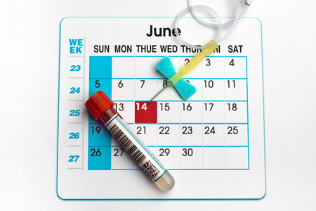 donor: blood tube and planning calendar with Blood Donor Day on June 14 highlighted  blood donor day June 14th Stock Photo