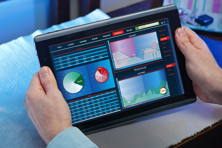 working hands: Man working with tablet while learning the charts statesmen consumer market  hands with touchpad while examines a market study Stock Photo