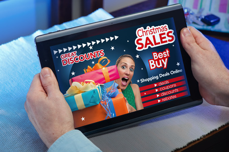 home store: man searching website internet store to purchase Christmas presents online in christmas with your tablet in you home  hands of a man in web tablet at a website with an announcement concept purchase Christmas presents online Stock Photo
