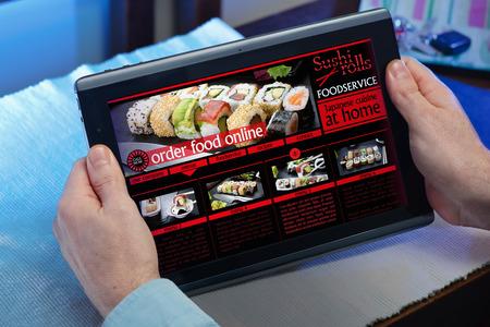 orden de compra: hombre que busca página web del restaurante Internet para comprar alimentos en línea con la tableta en su casa manos de un hombre en un sitio web de un servicio de entrega de comida de restaurante en la tableta