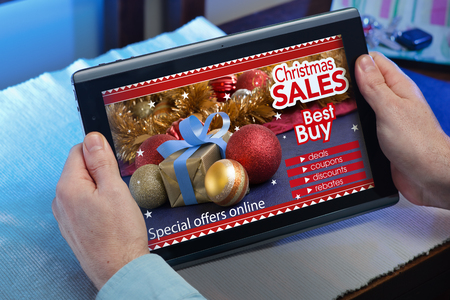 man searching website internet store to purchase christmas gifts online with your tablet in you home