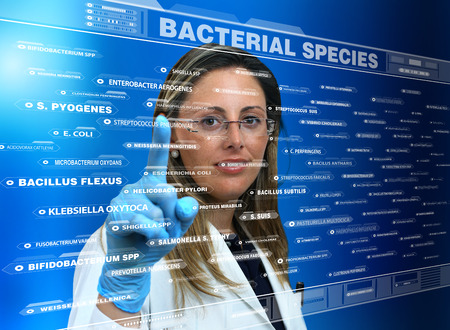 bacteriology: female doctor touching the interface of a virtual application where a list of species of bacteria  woman doctor using a virtual touch screen interface with a list of diseases Stock Photo