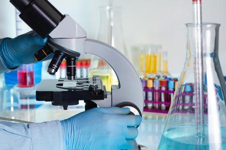 wetenschapper op zoek door een microscoop in het lab Stockfoto