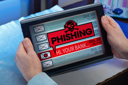 web scam: man with tablet which see an alert message with the word phishing  hands of a man looking emails in tablet with a virus message Stock Photo