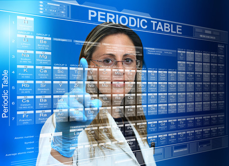 researcher woman with periodic table on virtual touch screen interface  Scientific female touching a virtual screen with the periodic table