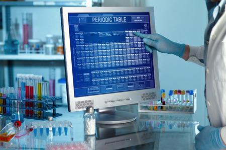 Laboratorio con un investigador de la tabla periódica en el trabajo científico en el laboratorio de la pantalla del ordenador y tocar una pantalla con la tabla periódica