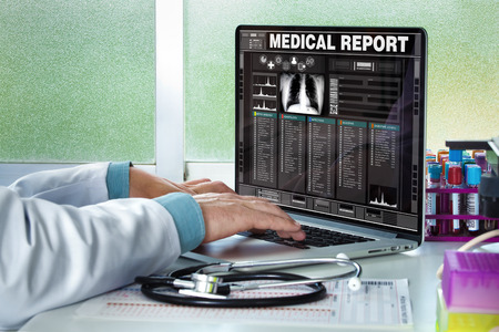 clinical: physician in consultation with a medical record of a patient on the screen of the laptop  Doctor consulting a medical history on a computer Stock Photo