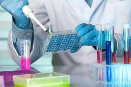 Scientist in lab holding a 96 well plate with samples for analysis / hand of a researcher pipetting samples in microplates