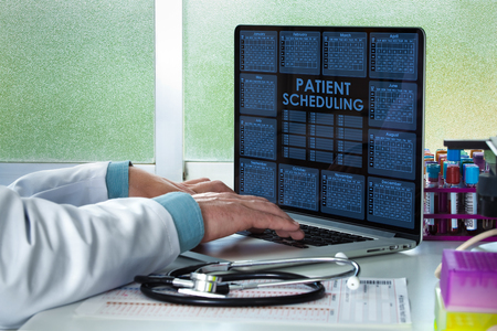 doctor appointment: doctor with computer in the medical office with the interface of a application agenda  doctor with laptop interface with a calendar medical