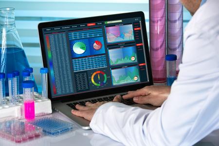 científico que trabaja con el ordenador portátil en el laboratorio de ingeniería / biomédica trabaja con el ordenador en el laboratorio