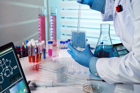 researcher working in a biotechnology lab / biochemical engineer working with microplate in a laboratory experiment