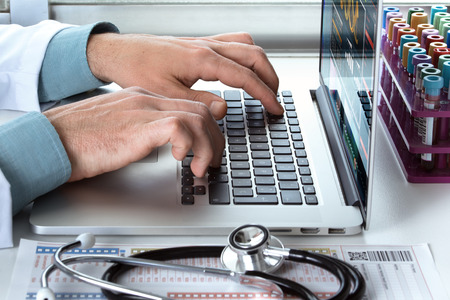 practitioner typing on laptop at medical consultation  doctors hands using laptop at medical office