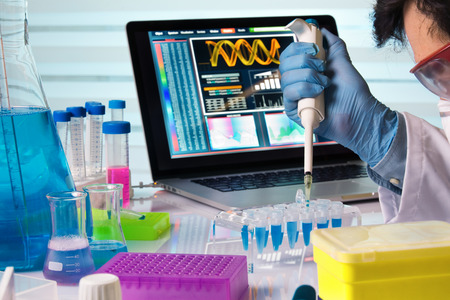 scientist holding tube and working with laptop in genetics lab / engineer genetic working in laboratory with pipette