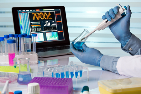 científico de la celebración matraz y trabajar con el portátil en el ingeniero de laboratorio / químico trabaja en el laboratorio con la pipeta y el frasco Foto de archivo