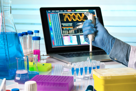 scientist holding dropper and working with laptop in genetics lab  researcher hands working with pipette and tubes in the laboratory table