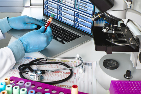 doctor testing blood tube in the laboratory / hands of a scientist holding blood tube sample in hematology lab Standard-Bild