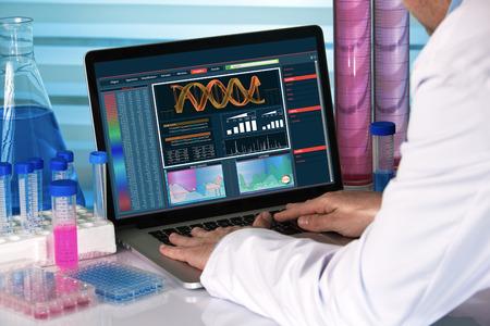 ingeniero genético que trabaja con el software de análisis de ADN en la computadora portátil en el laboratorio de genética / genetista usando equipo de laboratorio de biotecnología Foto de archivo