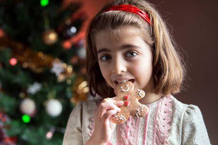 Mädchen zu Hause mit einem süßen Weihnachten in der Hand und der Weihnachtsbaum im Hintergrund / kleines Mädchen essen ein Lebkuchen Cookie vor dem Weihnachtsbaum