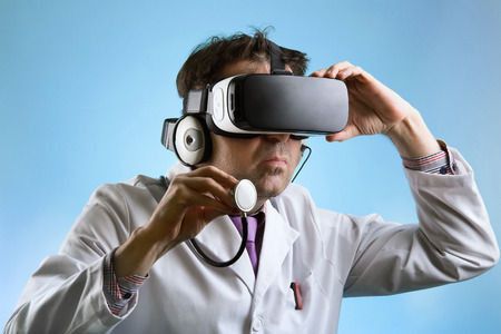 medical practitioner: Practitioner in virtual medical tour with VR virtual reality glasses  Doctor wearing virtual reality glasses conducting a remote clinical consultation Stock Photo