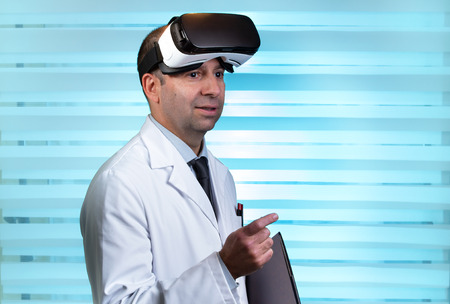 Practitioner with VR virtual reality glasses  Doctor wearing virtual reality glasses in clinical consultation Stock Photo