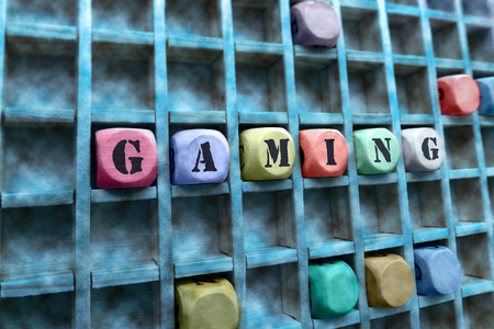 letterpress type: Composition of the word Gaming with wooden cubes in square box  Gaming word made with building wooden blocks