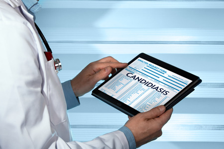 gynecologist with medical record digital on the tablet with candidiasis in diagnostic / urologist holding tablet with a candidiasis diagnosis in digital medical report Imagens