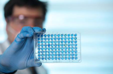 Scientist in lab holding a 96 well plate for analysis  researcher in the laboratory holding samples in microplate