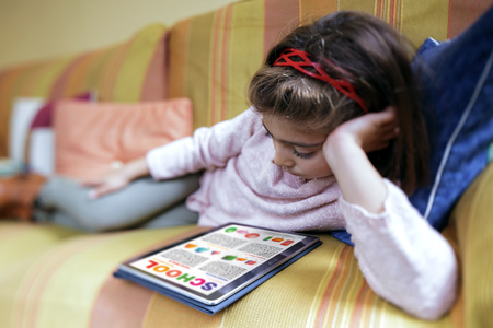 girl student reading relaxed in her tablet computer the school work  education concept. Little girl lying on the sofa at home studying home work on the tablet Stock Photo