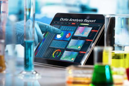 Expérience de travail scientifique avec un ordinateur dans le laboratoire / chercheur travaillant avec un rapport d'analyse de données dans une tablette numérique du laboratoire