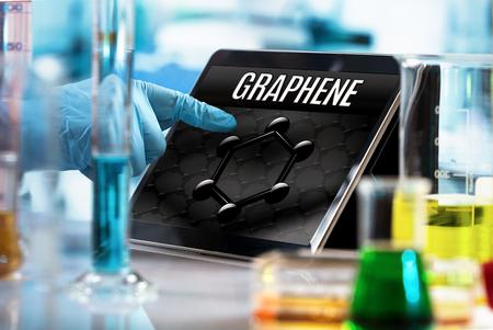 badacz technologii pracujący w laboratorium z ekranem komputerowym i koncepcyjnym przedstawieniem materiału grafenowego / inżynier pracujący w laboratorium badawczym z tabletem i symbolem grafenu na ekranie