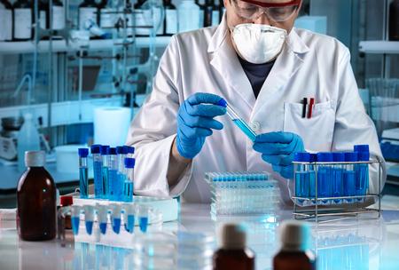 investigador que sostiene el tubo en el laboratorio químico / científico trabaja en el laboratorio de investigación
