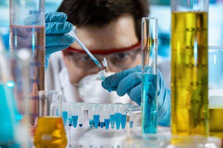 Investigador sosteniendo el tubo de ensayo para el análisis con material químico en el laboratorio de investigación / ingeniero químico pipeteando muestras en tubo pcr en el laboratorio de investigación