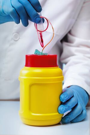 Doctor removed material used in a blood draw in a biohazard waste container / Hand of a laboratory technician removing material in a sharps container