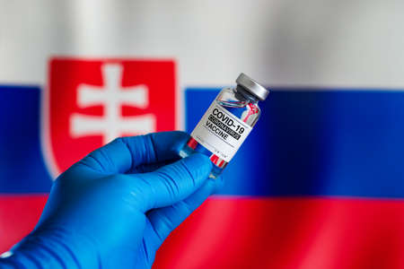 Doctor with vial of the vaccine for covid-19 and Slovakia flag in the background. Vial of vaccine for the vaccination against coronavirus plan in Slovakia Standard-Bild