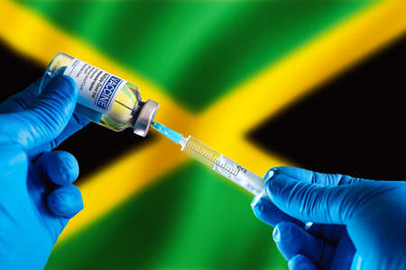Doctor preparing vial of vaccine injection for the vaccination plan against diseases in Jamaica. Injecting dose of vaccine in syringe for infections prevention in front of the Jamaica flag Standard-Bild