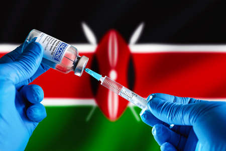 Doctor preparing vial of vaccine injection for the vaccination plan against diseases in Kenya. Injecting dose of vaccine in syringe for infections prevention in front of the Kenya flag
