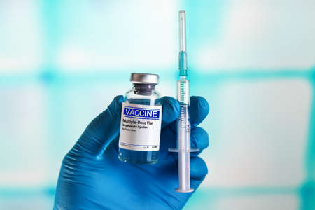 Hand with generic injectable vaccines vial for the vaccination program against diseases and infections prevention. doctor holds the hand Vaccine vial and syringe to administer vaccination doses to the population