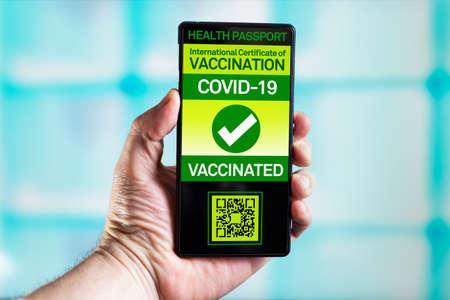 Traveler shows health passport with vaccination certification against coronavirus disease. Phone of Tourist with immunity passport software that certifies their vaccination against the COVID-19 virus Standard-Bild