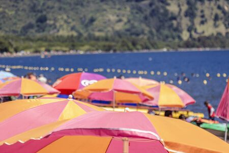 overcrowded: Colored beach umbrellas in a beach near a lake in the Araucania, Chile. Stock Photo